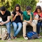 Handysucht - HypnoBeep hilft! Group of teenage boys and girls ignoring each other while using their cell phones at school